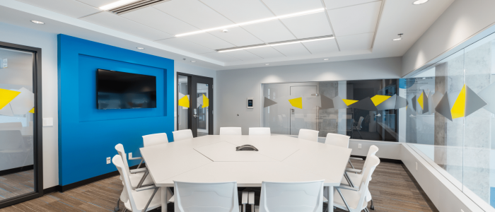 A boardroom with a white table and chairs in the center. On the left there is a large tv on a blue wall. The right wall and back walls are glass and have yellow and grey designs along them.