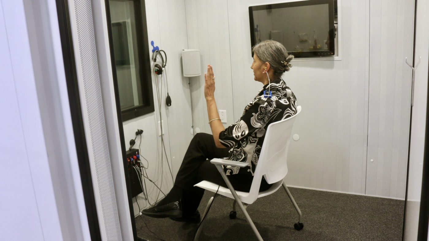 Woman sitting on chair facing westward with left hand raised up inside a white audiology studio booth with a TV to her right