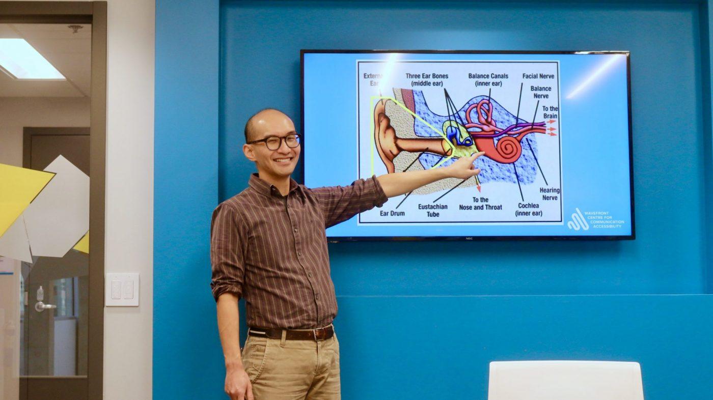 Man pointing towards the TV where it is displaying the anatomy of the ear. His finger is pointing to the cochlea (inner ear)