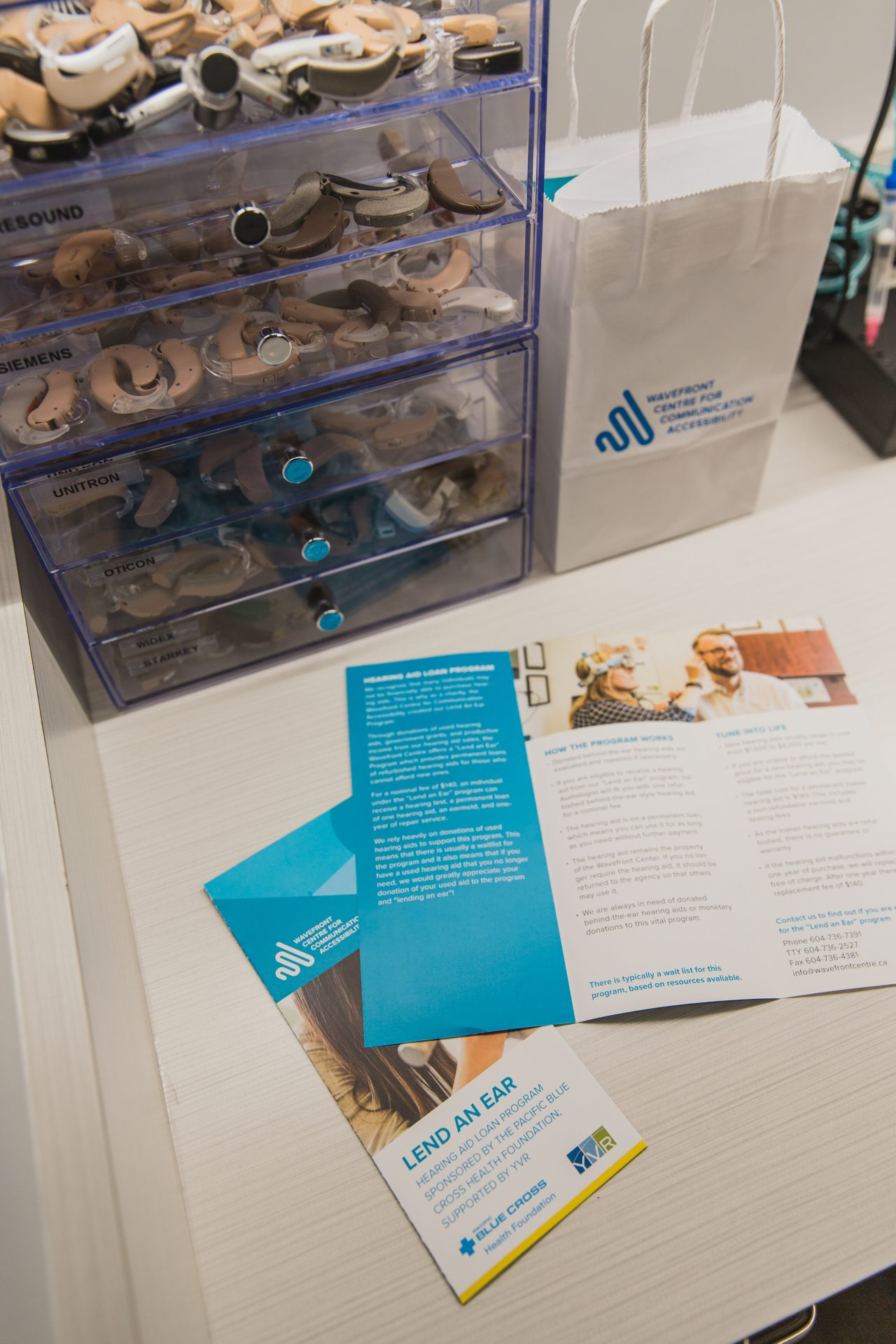 Display with six drawers all filled with hearing aids. On the counter is two Lend an Ear pamphlets