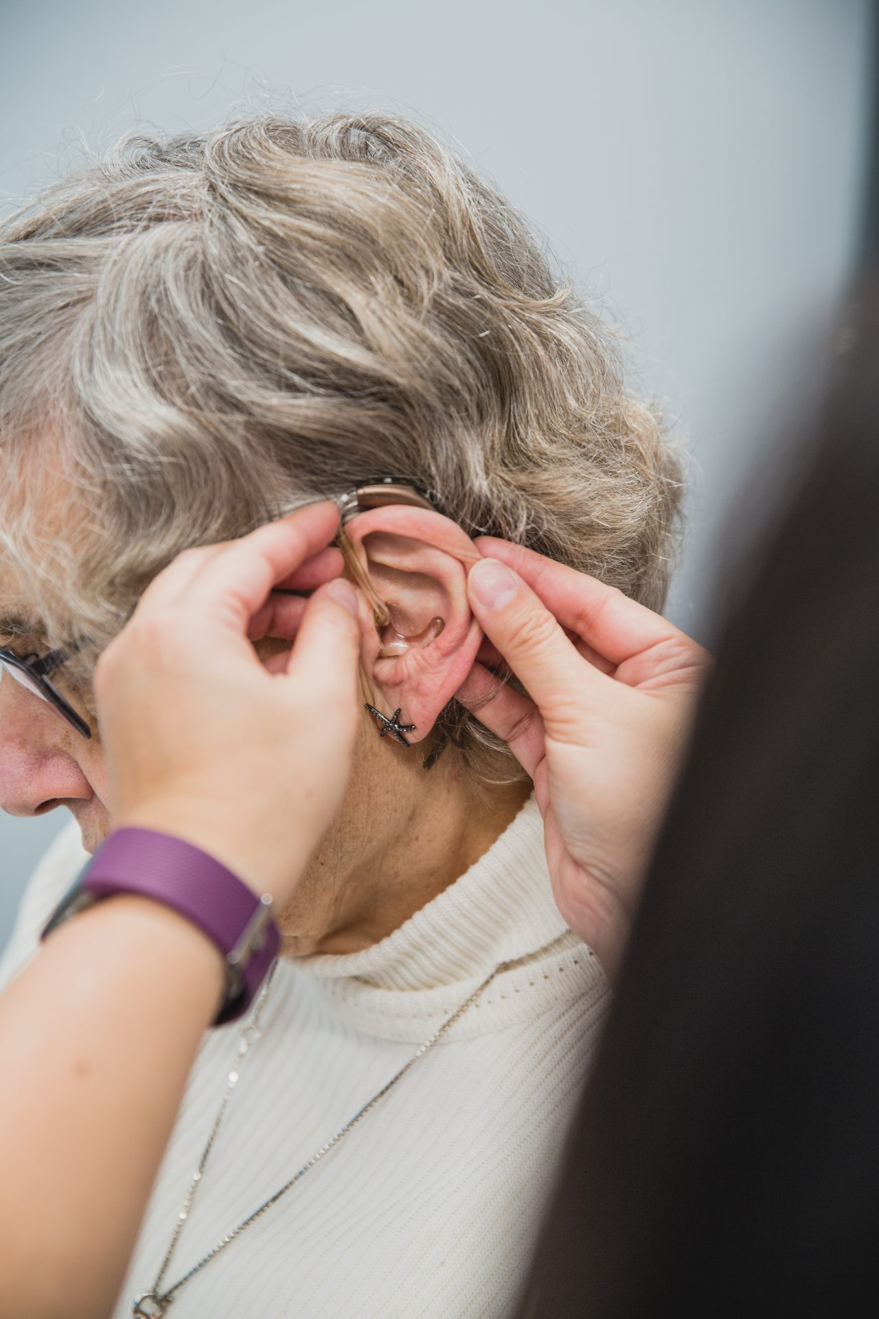 Woman has hearing aid placed on ear.